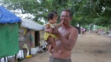 Father holding baby in shanty Footage