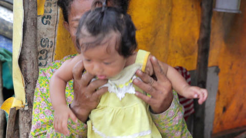 Mother feeding baby in slums Stock Video Footage