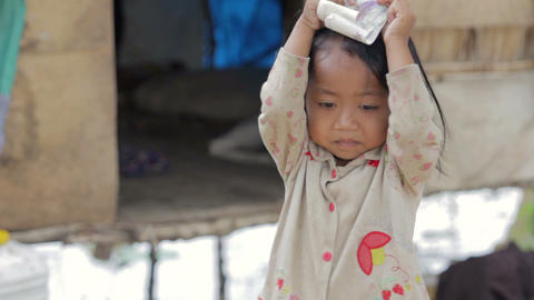 Cambodian kid holding money in slum Stock Video Footage