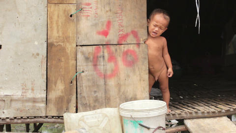 Naked baby crying in shack Footage