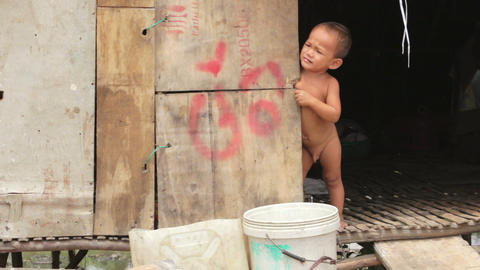 Naked baby crying in shack Stock Video Footage