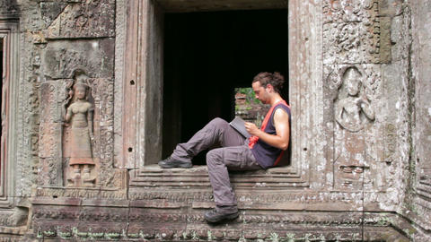 tourist reading book in angkor Stock Video Footage
