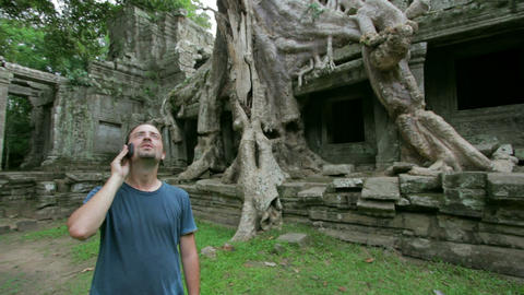 Young man talking phone in angkor Stock Video Footage