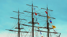 Three-masted frigate ship with colorful flags fluttering in the wind on the rigg Footage