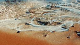 Foamy waves wash little rocks on a sandy beach Footage
