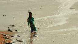 Metal peg with a scrap of fishing net washed by sea waves during high tide Footage