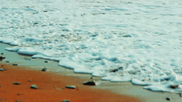 White foaming waves covers the sandy beach on a bright sunny day Footage