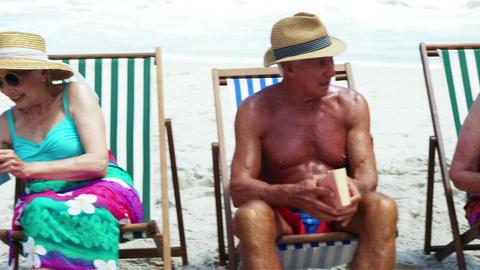 Senior friends sitting in beach chair Footage