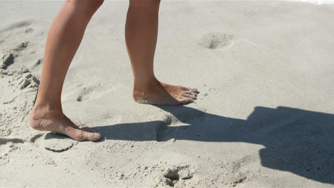 Woman walking on the beach bare footed Live Action