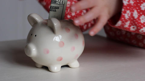 Girl Places Dollar Bill into Piggy Bank Footage