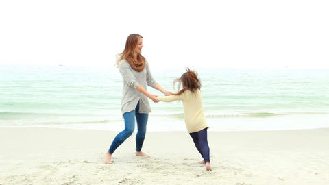 Mother and daughter playing on the beach Footage