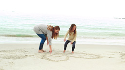 Mother and daughter drawing on the sand Footage