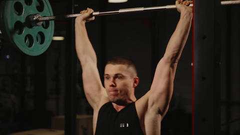 Sports inflated male performs the lifting weights performing standing exercise Filmmaterial
