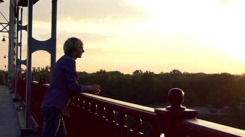 Young Man Stands on a Bridge Over The Dnipro River in Summer on a Sunny Day Live Action