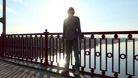 Young Man Stands And Smiles Near Handrails of a Bridge at Sunset in Slo-Mo Footage