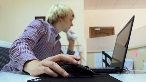 Young Man Works on a Laptop at an Office. he Takes a Telephone Suddenly Footage
