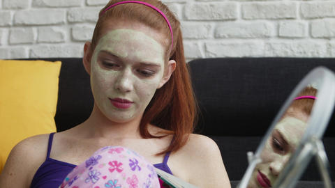 Teenager With Beauty Mask Reading Magazine And Relaxing Image