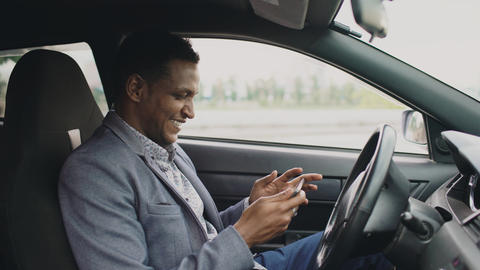 Happy african american businessman surfing social media on his tablet computer Photo