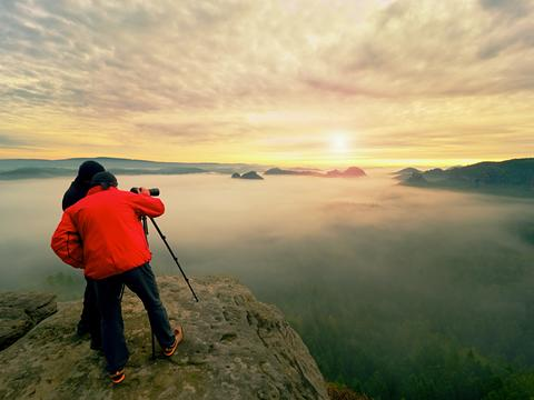 Photographer with eye at viewfinder of camera on tripod stay on cliff and takes Photo