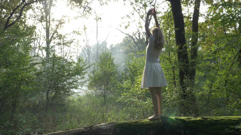 Woman doing yoga movements in the forest relaxing in nature Footage