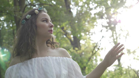 Beautiful young woman dressed in angelic fairy white dress contemplating nature Footage