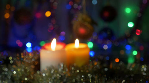 New Year's candles close-up. Blurred background with colored lights. Moving the Footage