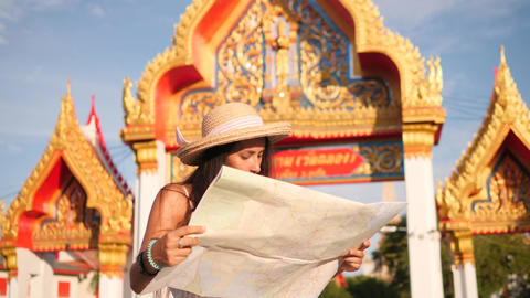 Young Mixed Race Tourist Woman Reading Map and Exploring Thai Buddhist Temple Footage