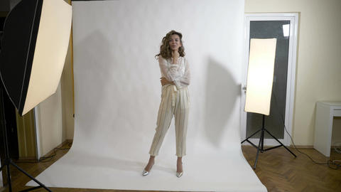 Attractive young fashion model with long hair posing in a professional studio Footage