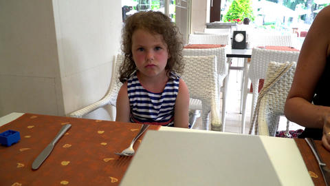 Pretty little girl sitting at kitchen table and gesturing with both hands Footage