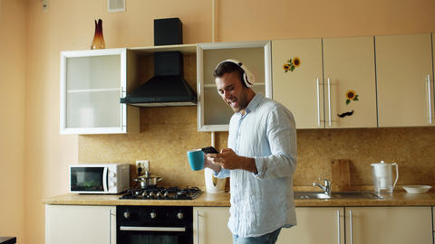 Handsome young funny man in headphones dancing and singing in kitchen at home in フォト