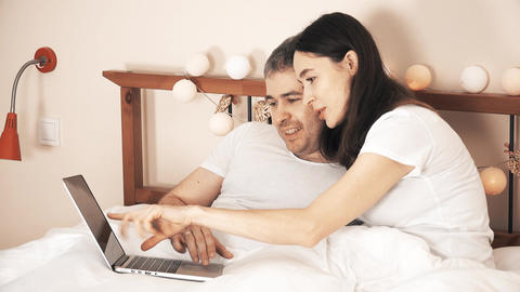 Joyful couple using their laptop in bed at home Footage