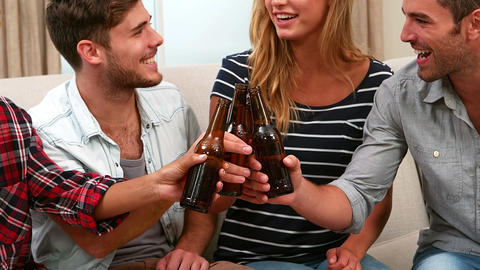 Smiling friends drinking beer together Footage