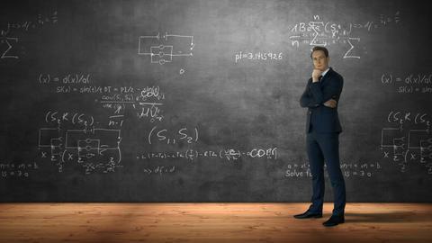 Businessman standing against formulas Footage