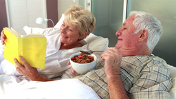 Senior couple reading book and eating cereal Footage