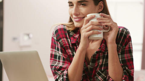 Smiling woman using laptop while drinking coffee Footage