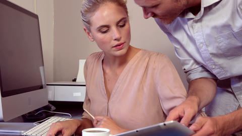 Serious woman working on computer while man showing tablet Footage