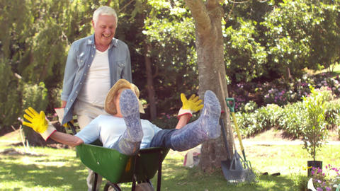 Husband pushing wife in a wheelbarrow Footage