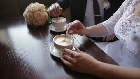 Young couple talking and drinking coffee during breakfast at cafe. They mixing Footage