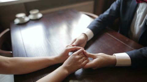 A pair of newlyweds holding hands in a cafe. Close up of human hands ビデオ