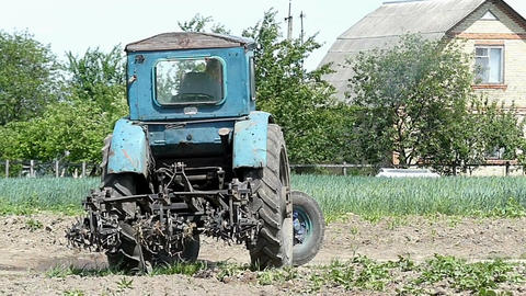 A middle-size tractor turns right with a raises harrow in summer Footage