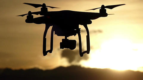 A soaring quadracopter with rotating blades at a nice sunset Footage
