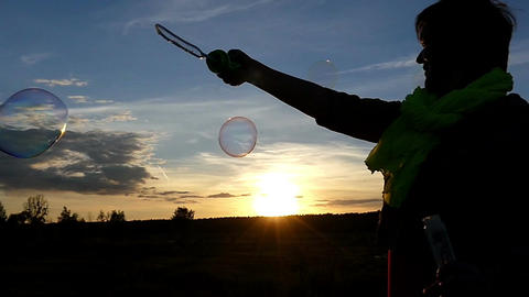 A cheery woman makes soap bubbles at sunset in slo-mo Footage