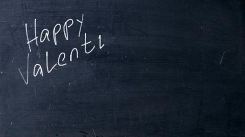 Happy Valentines Day hand drawn white chalk at black school chalkboard. Heart Live Action