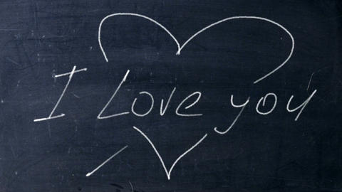 I love you. Handwritten chalk on a black chalkboard. Arrow shot heart shape Footage
