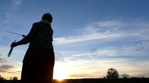 A woman makes soap bubbles while turning her hand at susnset Footage