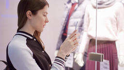 Young woman near window shop with mannequins. Reading QR-codes by smartphone Footage