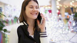 Woman in mall using mobile receiving congratulations on New Year. Christmas Footage