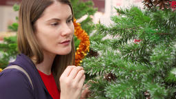 Happy cheerful woman buying Christmas decorations in mall. Female choosing faux Footage