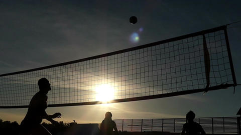 Sportive people playing volleyball at a network at sunset in slow motion Footage