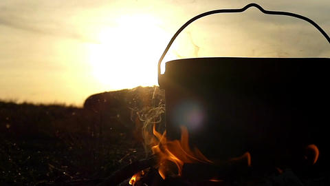 A cauldron with water stands in a bonfire at sunset in slo-mo Footage